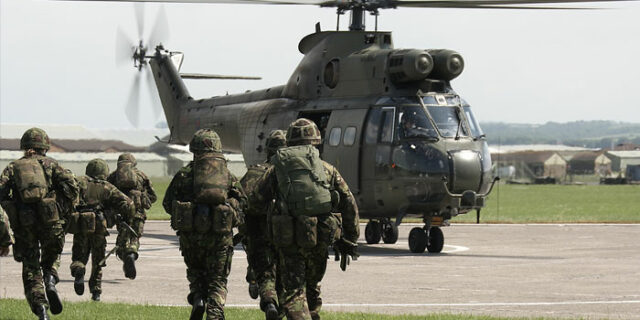 Soldiers running towards a helicopter