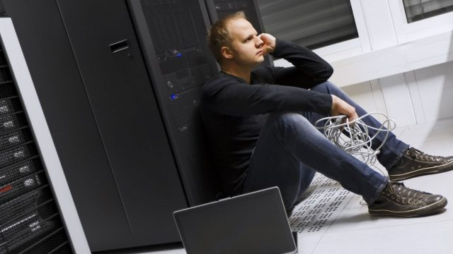 An IT professional looking concerned sat by a server